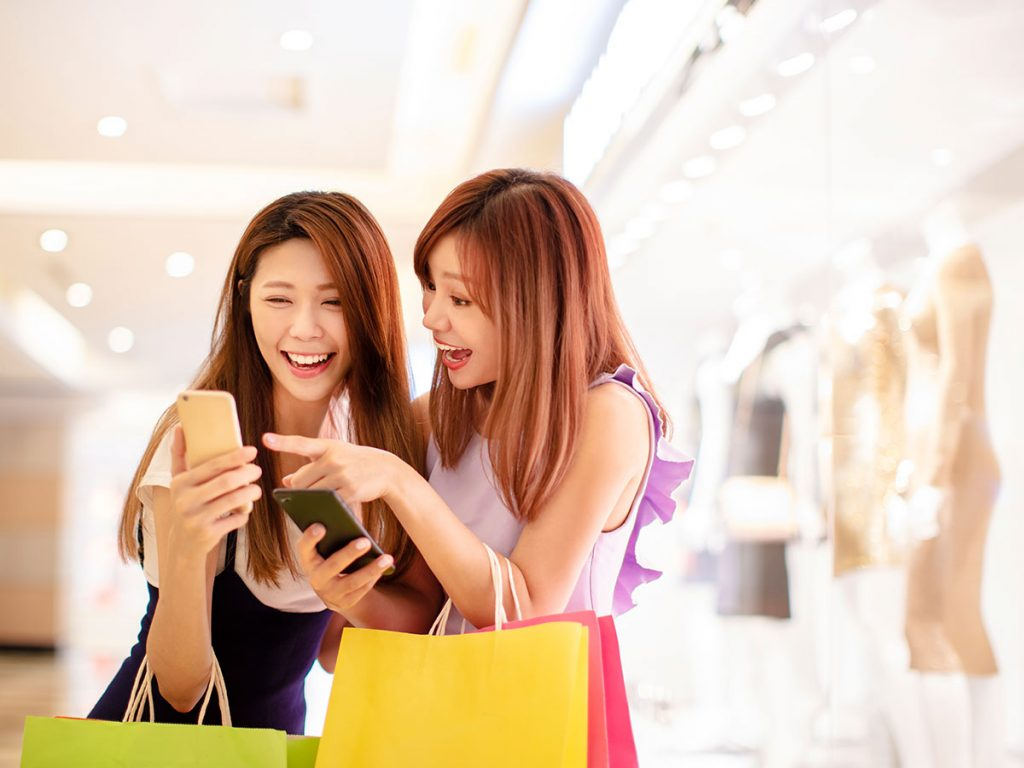 two engaged phone users on facebook while shopping